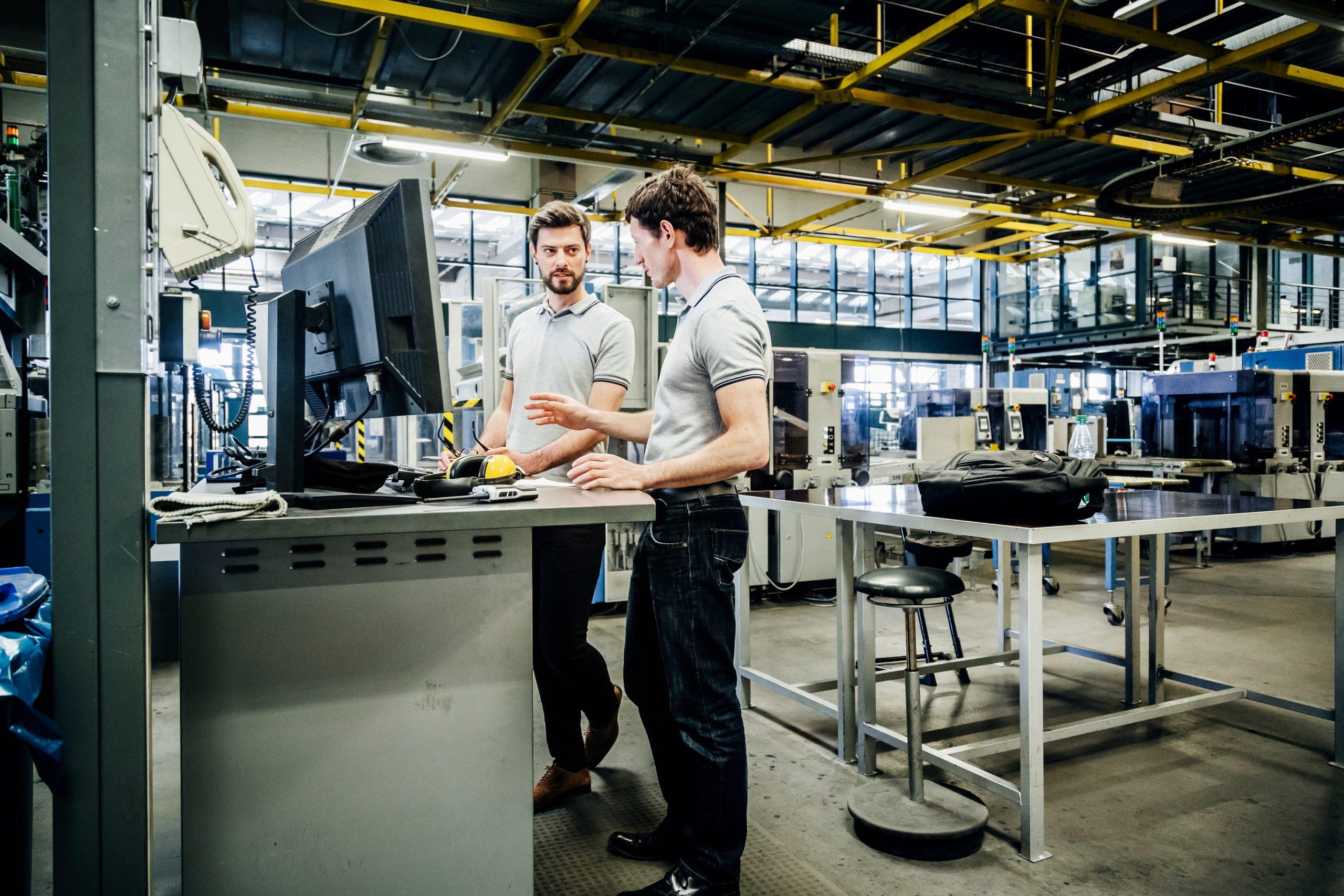 Deux collaborateurs travaillent debout devant leurs ordinateurs