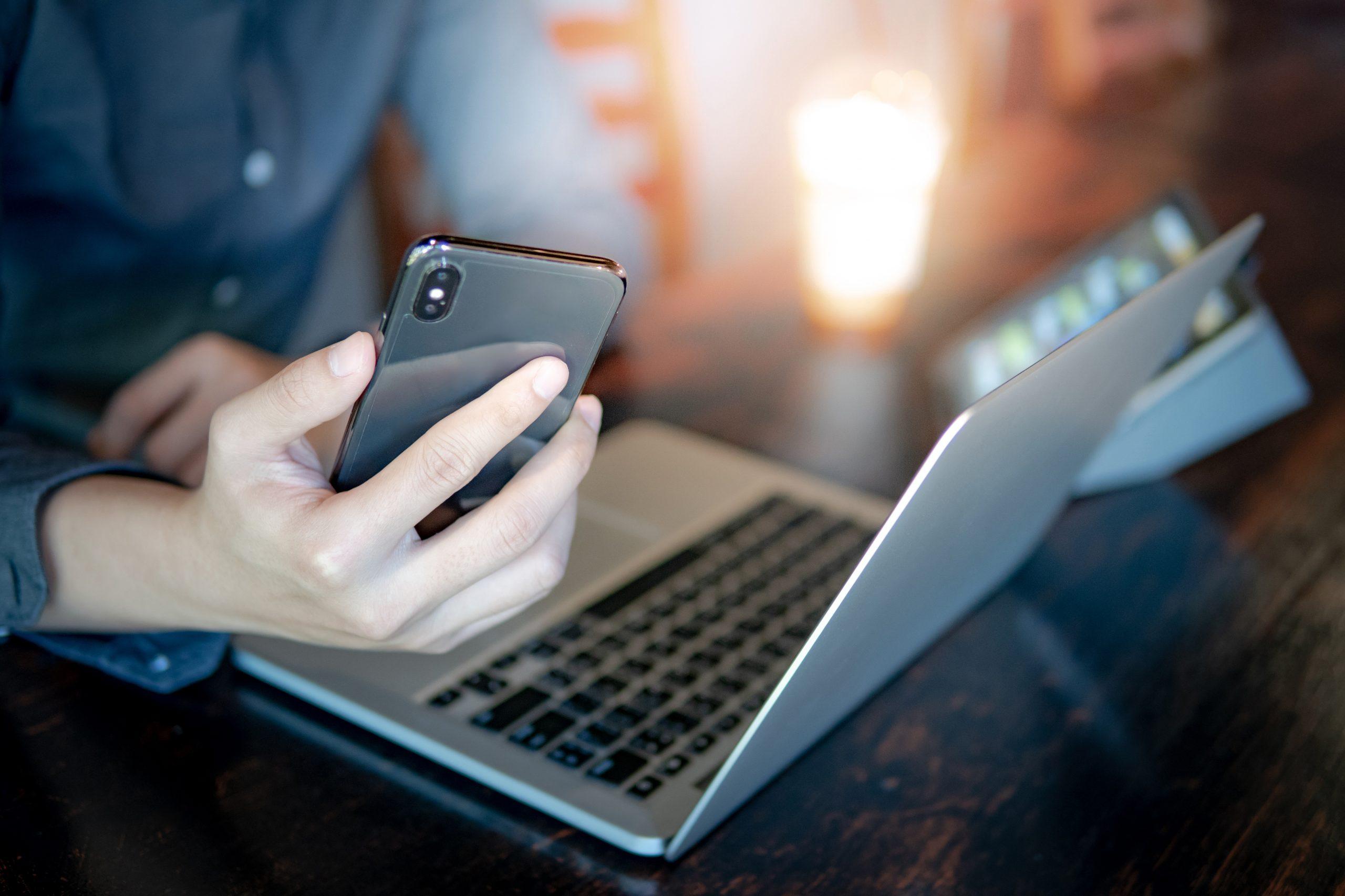 Collaborateur OGI qui travaille sur son ordinateur et tient son smartphone