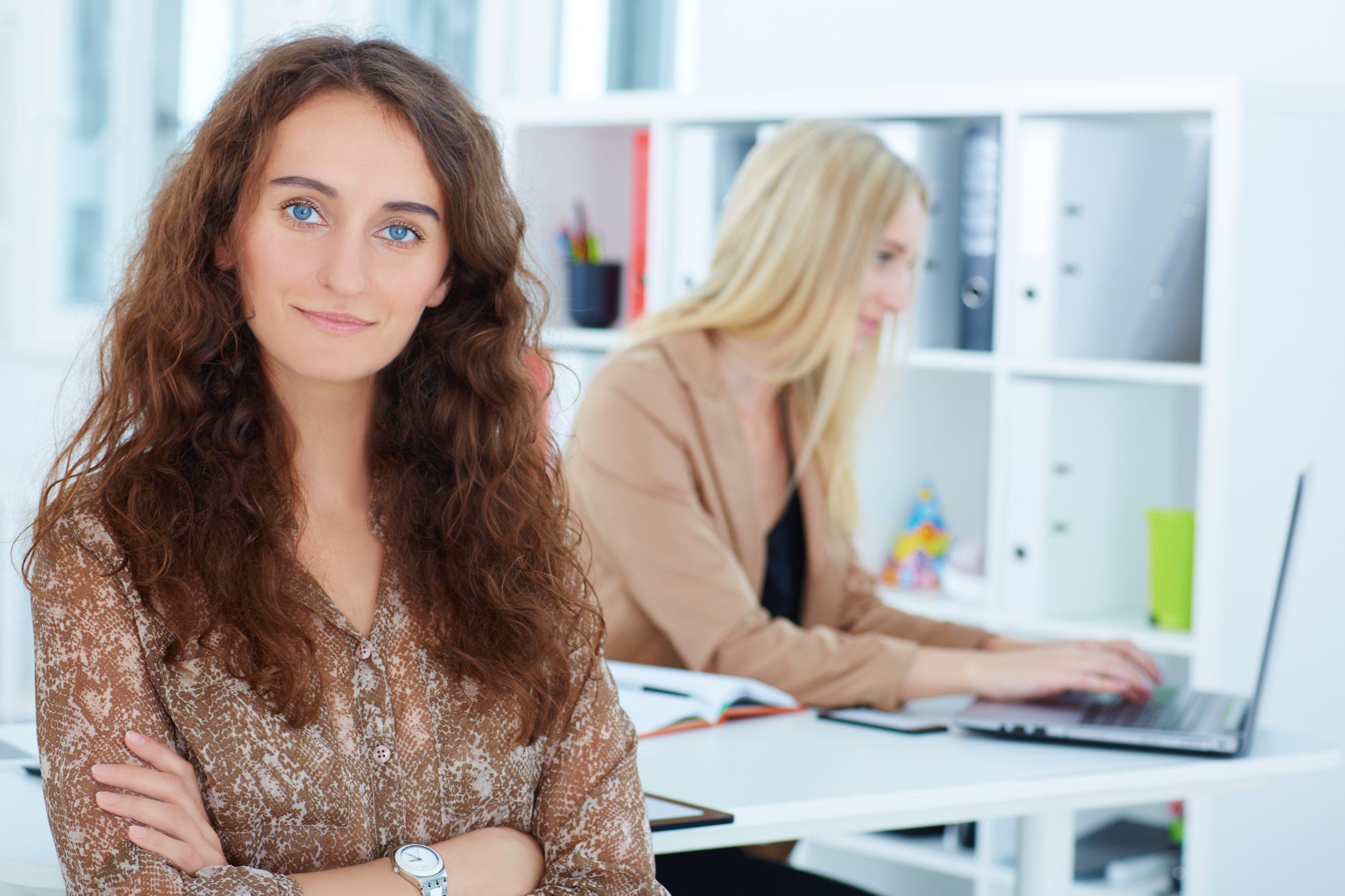Collaboratrice souriante devant une collègue qui travaille sur son ordinateur